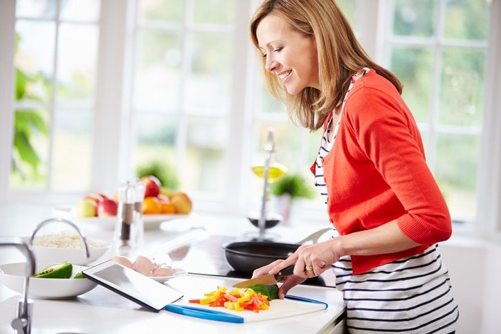 Woman in Kitchen Cooking Healthy to Avoid Metabolic Damage